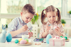 Two happy children having fun during painting eggs for easter in royalty free stock images