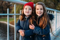 Two happy children hugging in autumn park. Close up sunny lifestyle fashion portrait of two beautiful caucasian girls outdoors,wea. Ring cute trendy outfit stock photo