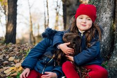 Two happy children hugging in autumn park. Close up sunny lifestyle fashion portrait of two beautiful caucasian girls outdoors,wea. Ring cute trendy outfit stock image