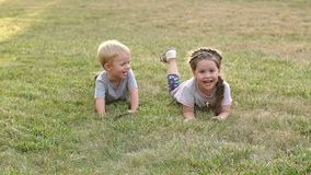 Two happy children lie on the grass in the park. Two happy children lie on the grass in the park and laugh stock video footage
