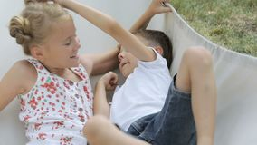 Two happy children lie on a hammock . Concept carefree childhood stock footage