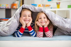 Two happy children lying under blanket Stock Photo