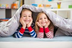 Two happy children lying under blanket Stock Photo