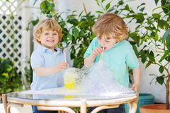 Two happy children making experiment with colorful bubbles. Two happy children making experiment with colorful soap bubbles and water, outdoors royalty free stock image