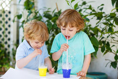 Two happy children making experiment with colorful bubbles. Two happy children making experiment with colorful soap bubbles and water, outdoors royalty free stock photography