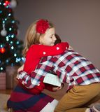 Two happy children in new year eve with presents near New Year T. Ree at home Royalty Free Stock Images
