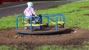 Two happy children play on roundabout at sunny day. N stock video
