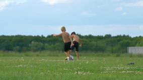 Two happy children play soccer on a sunny day on a green lawn. Blurred focus. Slow motion stock footage