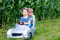 Two happy children playing with big old toy car in summer garden, outdoor. S. Boy driving car with little girl inside. Laughing and smiling kids. Family royalty free stock image