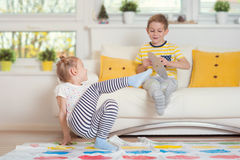 Two happy children playing exciting game at home Stock Photos