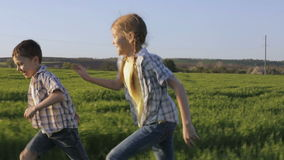 Two happy children playing in the field at the day time. Kid having fun outdoors. Concept of happy game stock footage