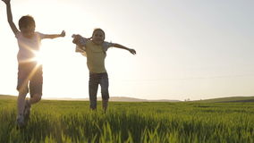 Two happy children playing in the field at the sunset time. Kid having fun outdoors. Concept of happy game stock video footage