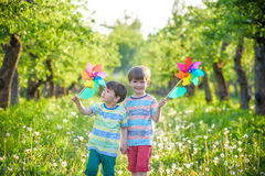 Two happy children playing in garden with windmill. Pinwheel. Adorable sibling brothers are best friends. Cute kid boy smile spring or summer park. Outdoors Stock Images