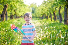 Two happy children playing in garden with windmill. Pinwheel. Adorable sibling brothers are best friends. Cute kid boy smile spring or summer park. Outdoors Royalty Free Stock Photo