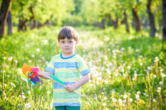 Two happy children playing in garden with windmill. Pinwheel. Adorable sibling brothers are best friends. Cute kid boy smile spring or summer park. Outdoors Stock Photography