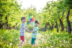 Two happy children playing in garden with windmill. Pinwheel. Adorable sibling brothers are best friends. Cute kid boy smile spring or summer park. Outdoors Stock Photo
