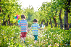 Two happy children playing in garden with windmill. Pinwheel. Adorable sibling brothers are best friends. Cute kid boy smile spring or summer park. Outdoors Royalty Free Stock Photos