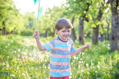 Two happy children playing in garden with windmill. Pinwheel. Adorable sibling brothers are best friends. Cute kid boy smile spring or summer park. Outdoors Royalty Free Stock Image