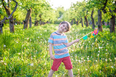 Two happy children playing in garden with windmill. Pinwheel. Adorable sibling brothers are best friends. Cute kid boy smile spring or summer park. Outdoors Royalty Free Stock Photography