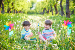 Two happy children playing in garden with windmill. Pinwheel. Adorable sibling brothers are best friends. Cute kid boy smile spring or summer park. Outdoors Royalty Free Stock Images