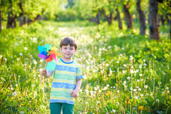 Two happy children playing in garden with windmill. Pinwheel. Adorable sibling brothers are best friends. Cute kid boy smile spring or summer park. Outdoors Stock Image