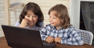 Two happy children playing with laptop outdoors.  royalty free stock photo