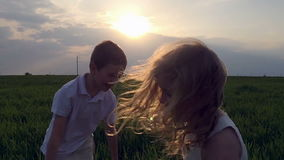 Two happy children playing on meadow, sunset. Summertime. Slow motion. Shot in 120 fps iphone 5s stock video