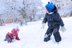 Two happy children playing snowball Stock Photos