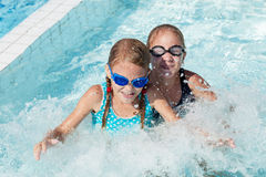 Two happy children playing on the swimming pool at the day time. Stock Photo