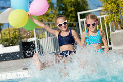 Two happy children playing on the swimming pool at the day time. Two happy children with balloons playing on the swimming pool in aqua park at the day time Stock Photos