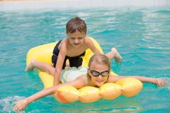 Two happy children playing on the swimming pool at the day time. Stock Photos