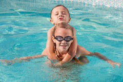 Two happy children playing on the swimming pool at the day time. Royalty Free Stock Images