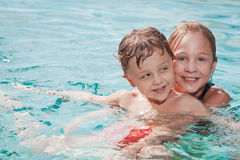 Two happy children playing on the swimming pool at the day time. Stock Images