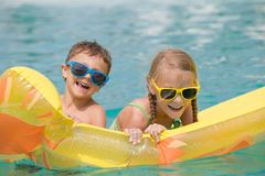 Two happy children playing on the swimming pool at the day time. Stock Image