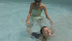 Two happy children playing on the swimming pool. At the day time. People having fun outdoors. Concept of friendly siblings stock footage