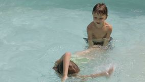 Two happy children playing on the swimming pool stock video footage