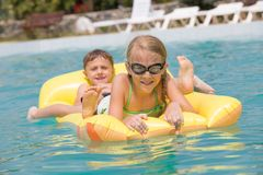 Two happy children playing on the swimming pool at the day time. Royalty Free Stock Image