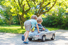 Two happy children playing with toy car Stock Photo