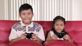 Children playing video games at home. Two happy children playing video games while sitting on the sofa in the living room at home stock video