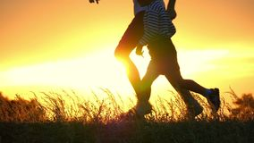 Two happy children running after each other against the sunset. The two brothers are playing catch-up in a slow motion. The camera removes the legs and trunk stock video footage