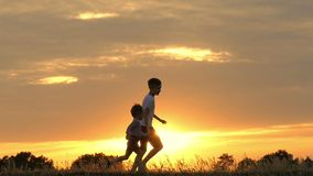 Two happy children running after each other against the sunset. The two brothers are playing catch-up in a slow motion. Slow motion stock footage