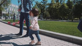 Two happy children running in summer park. Two little girls are running around the green grass in the center of the city. a walk of two sisters through the city stock footage