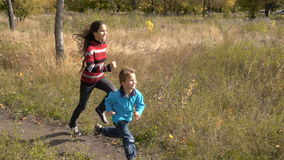 Two children running together on autumn park. Two happy children running together on sunny autumn park stock footage