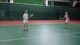 Two happy children serving and returning balls training skills on court with rackets. Pretty boy and girl playing sport. Two happy children serving and returning stock footage