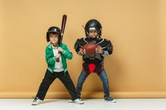Two happy children show different sport. Studio fashion concept. Emotions concept. Two happy boys showing different sport. Studio fashion concept. Emotions Royalty Free Stock Photos