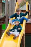 Two happy children  on slide at playground. In autumn Stock Photos