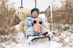 Two happy children in winter fashion clothes ride a sleigh with a toy pig and a bear on a bridge across the river. First snow, fam Stock Photos