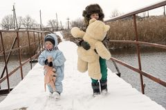 Two happy children in winter fashion clothes ride a sleigh with a toy pig and a bear on a bridge across the river. First snow, fam Stock Photo