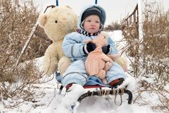 Two happy children in winter fashion clothes ride a sleigh with a toy pig and a bear on a bridge across the river. First snow, fam. Ily, tradition, holiday Royalty Free Stock Photo