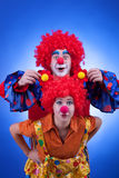 Two happy clowns playing on blue background Royalty Free Stock Photos